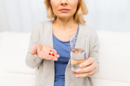 health care and medicine: medicine, health care and people concept - close up of middle aged woman with medicine and water glass at home Stock Photo
