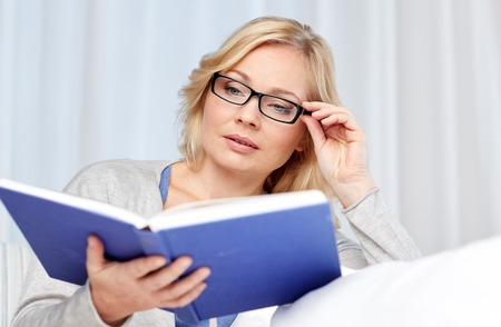 woman  glasses: leisure, literature and people concept - middle aged woman reading book and sitting on couch at home