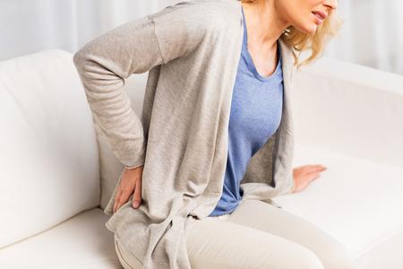人々 のヘルスケアそして問題のコンセプト - 背部の痛みまたは手綱を自宅から苦しんでいる不幸な女性のクローズ アップ