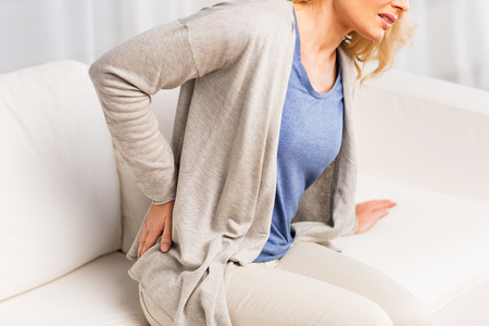 female back: people, healthcare and problem concept - close up of unhappy woman suffering from pain in back or reins at home