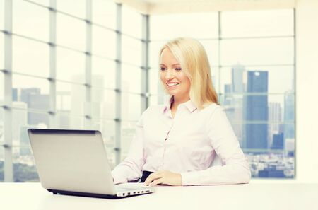 view of an elegant office: education, business and technology concept - smiling businesswoman with laptop computer over office room with city view window background Stock Photo
