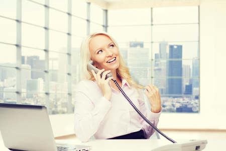 chatty: business, communication, people and technology concept - smiling businesswoman or secretary with laptop computer calling on telephone over office room with city view window background Stock Photo