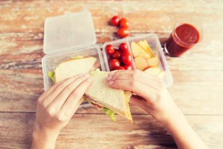 woman eat: healthy eating, storage, dieting and people concept - close up of woman hands with food in plastic container at home kitchen