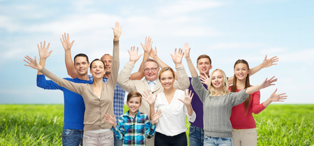three hands: family, gender, generation and people concept - group of smiling men, women and boy waving hands over blue sky and grass background