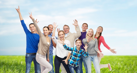 grass and sky: family, gender, generation and people concept - group of smiling men, women and boy having fun and waving hands over blue sky and grass background