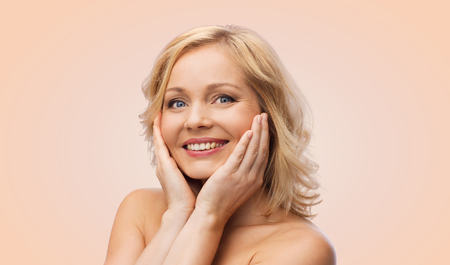 bare shoulders: beauty, people and skincare concept - smiling woman with bare shoulders touching face over beige background Stock Photo