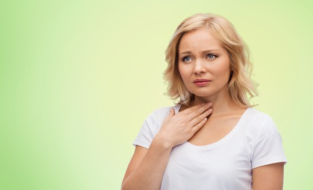 people, healthcare and problem concept - unhappy woman touching her neck and suffering from throat pain over green natural background