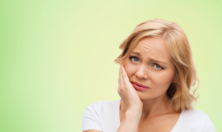 people, healthcare, dentistry and problem concept - unhappy woman suffering toothache over green natural background