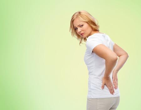 las personas, la salud, dolor de espalda y el concepto de problema - infeliz mujer que sufre de dolor en la espalda u riendas sobre el fondo verde natural