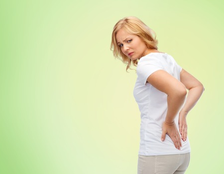 back ache: people, healthcare, backache and problem concept - unhappy woman suffering from pain in back or reins over green natural background