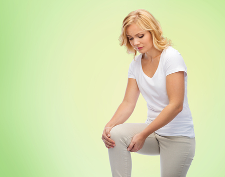 middle joint: people, healthcare and problem concept - unhappy middle aged woman suffering from pain in leg or knee at home over green natural background Stock Photo