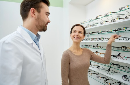 health care decisions: health care, people, eyesight and vision concept - happy woman choosing and showing glasses to optician at optics store