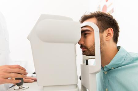 examen de la vista: cuidado de la salud, la medicina, la gente, la vista y la tecnología concepto - cerca de un optometrista con autorrefractor comprobar la visión del paciente en la clínica de los ojos o la óptica tienda