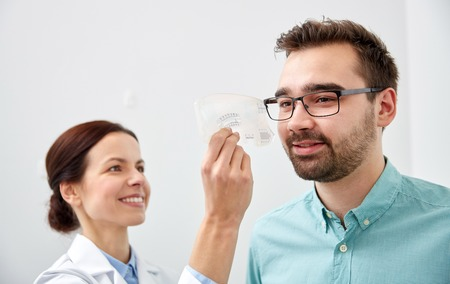 health care, medicine, people, eyesight and technology concept - optometrist with scale checking patient sight eye clinic or optics store Stock Photo