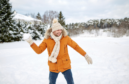 snowballs: people, season and leisure concept - happy young man playing snowballs in winter