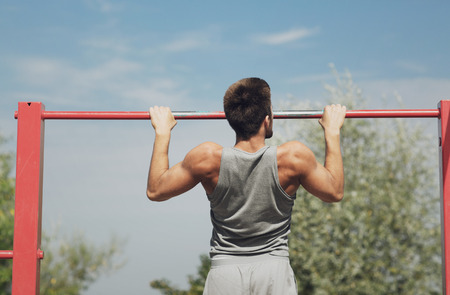 pull up: fitness, sport, exercising, training and lifestyle concept - young man doing pull ups on horizontal bar outdoors