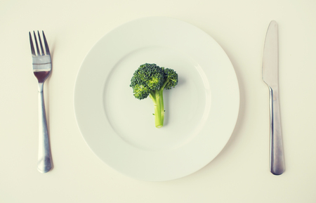 diet food: healthy eating, diet, vegetarian food and culinary concept - close up of broccoli on plate