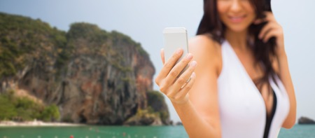 bali beach: summer, travel, technology and people concept - close up of sexy young woman taking selfie with smartphone over bali beach and rock background