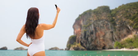 copies: summer, travel, technology and people concept - sexy young woman taking selfie with smartphone over bali beach and rock background Stock Photo