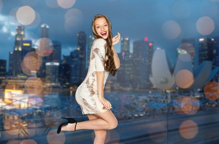 cheerful: people, style, holidays, night life and fashion concept - happy young woman or teen girl in fancy dress with sequins and long wavy hair posing Stock Photo