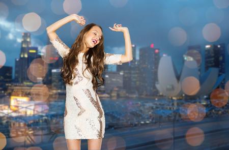 donna che balla: persone, vita notturna, vacanze e concetto di moda - felice giovane donna o adolescente ragazza in abito fantasia con paillettes e lunghi capelli ondulati ballare alla festa Archivio Fotografico