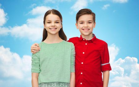 kinderjaren, vriendschap en mensenconcept - gelukkig glimlachend jongen en meisje die over blauwe hemel en wolkenachtergrond koesteren Stockfoto