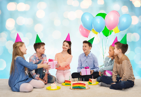 birthday presents: childhood, holidays, celebration, friendship and people concept - happy smiling children in party hats with cake giving presents at birthday party over blue holidays lights background