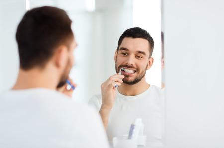 higiene bucal: cuidado de la salud, higiene dental, las personas y el concepto de belleza - hombre joven sonriente con los dientes de limpieza cepillo de dientes y que mira al espejo en el cuarto de baño casero