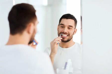 oral care: health care, dental hygiene, people and beauty concept - smiling young man with toothbrush cleaning teeth and looking to mirror at home bathroom Stock Photo