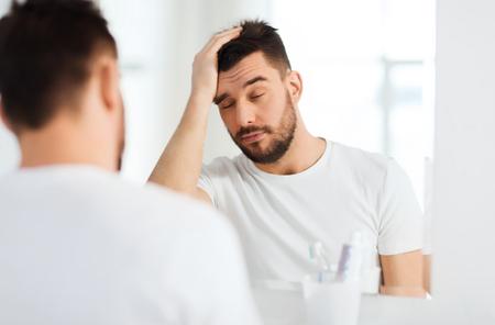 утро, пробуждение, похмелье и люди концепции - сонный молодой человек перед зеркалом в ванной