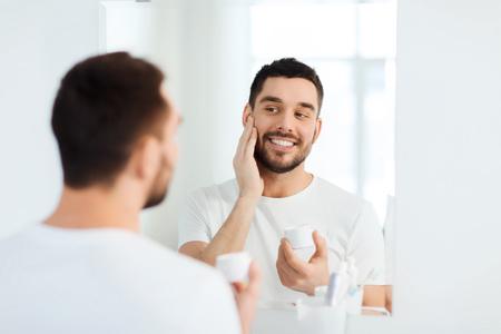 bellezza, cura della pelle e persone Concetto - sorridente, giovane, applicare la crema su viso e guardando a specchio in bagno di casa
