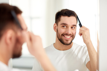 comb hair: beauty, grooming and people concept - smiling young man looking to mirror and brushing hair with comb at home bathroom