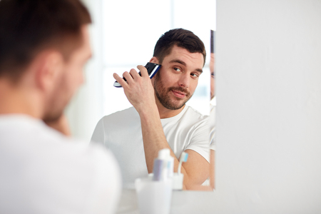 routine: beauty, hygiene, shaving, grooming and people concept - young man looking to mirror and shaving beard with trimmer or electric shaver at home bathroom