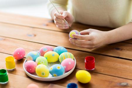 Pascua, días de fiesta, tradición y gente concepto - cerca de la mujer de las manos para colorear los huevos de Pascua con colores y pincel Foto de archivo