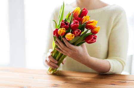 red hand: people, holidays and gardening concept - close up of woman holding tulip flowers