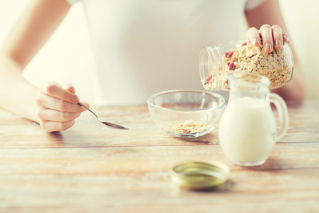 oatmeal bowl: food, healthy eating, people and diet concept - close up of woman eating muesli with milk for breakfast Stock Photo