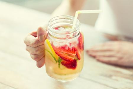 gesunde Ernährung, Getränke, Ernährung, Entgiftung und Konzept Menschen - in der Nähe der glücklichen Frau hält ein Glas mit Fruchtwasser zu Hause nach oben
