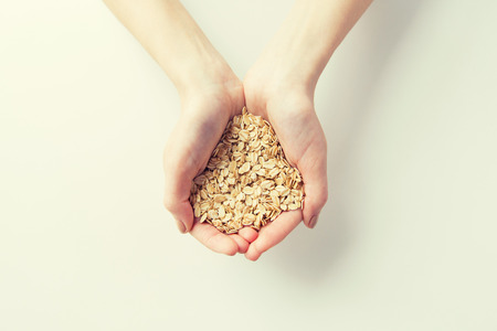 female hands: healthy eating, dieting, vegetarian food and people concept - close up of woman hands holding oatmeal flakes at home Stock Photo