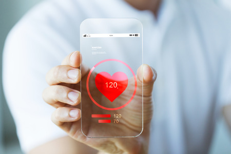 health technology: business, technology, health care and people concept - close up of male hand holding and showing transparent smartphone with heart rate icon