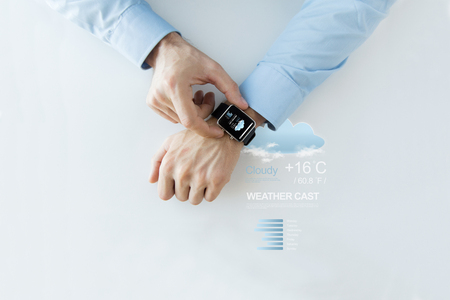 meteo: business, technology, weather forecast, application and people concept - close up of male hands setting smart watch with meteo cast on screen