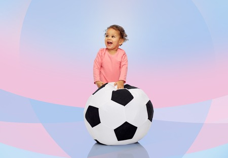 american sport: childhood, game, sport, football and people concept - happy african american little baby girl playing with ball over pink violet background Stock Photo