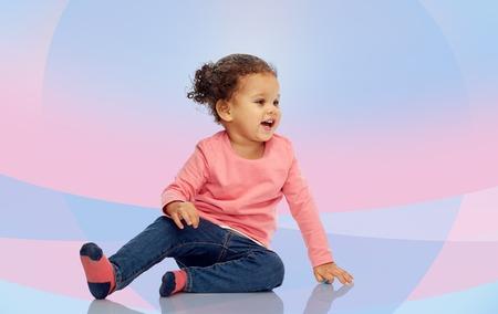 bebes niñas: la infancia, la moda, la ropa y el concepto de la gente - la sonrisa hermosa pequeña niña afroamericana sentado en el suelo sobre el fondo de color rosa violeta