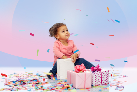 child birthday: childhood, birthday, party, holidays and people concept - happy little african american baby girl with gift boxes and confetti playing with shopping bag sitting on floor over pink violet background Stock Photo