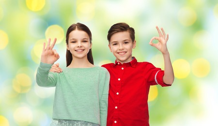 summer sign: childhood, friendship, summer holidays, gesture and people concept - happy smiling boy and girl hugging and showing ok hand sign over green lights background Stock Photo