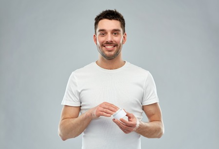the well groomed: beauty, skin care, body care and people concept - smiling young man with cream jar over gray background Stock Photo