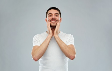 aftershave: beauty, skin care, grooming and people concept - happy young man touching his face applying aftershave over gray background