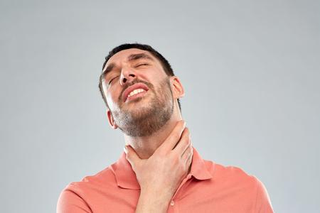 Menschen, Gesundheitswesen und Problem-Konzept - unglücklicher Mann seinen Hals und leidet an Halsschmerzen über grauem Hintergrund zu berühren