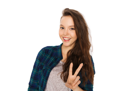 people and teens concept - happy smiling pretty teenage girl showing peace sign