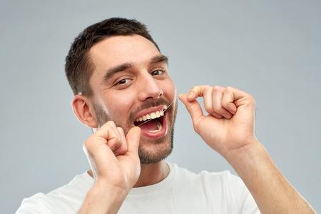 cuidado de la salud, higiene dental, la gente y el concepto de belleza - hombre joven y sonriente con los dientes de limpieza de la seda sobre fondo gris