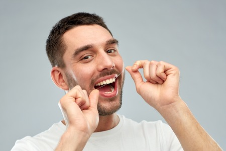 morning routine: health care, dental hygiene, people and beauty concept - smiling young man with floss cleaning teeth over gray background